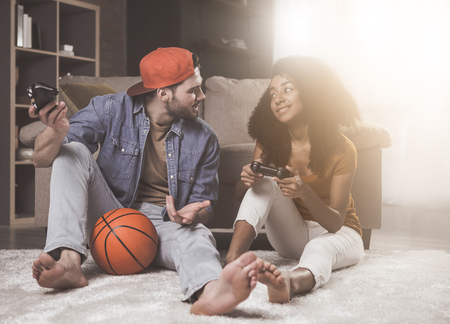 Fun together. Full length of pleasant stylish romantic guy and girl are talking and playing on console. They are sitting on floor at home with basket ball