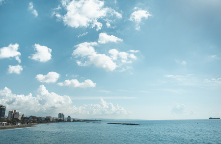 Endless blue sky with white fluffy clouds locating over blue sea and city. Landscape concept