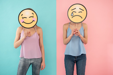 Waist up of smiling and crying female friends posing together. blue and pink background 写真素材