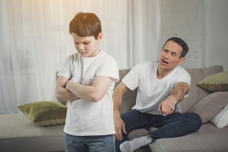 You are punished. Irritated father is yelling at his son. Abused child is standing with crossed arms in room