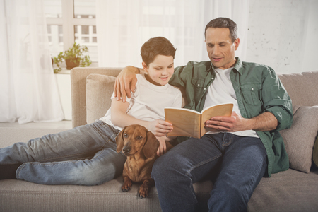 Cheerful father and son reading book together in living room. They are embracing and smiling. Positive dog is lying near them