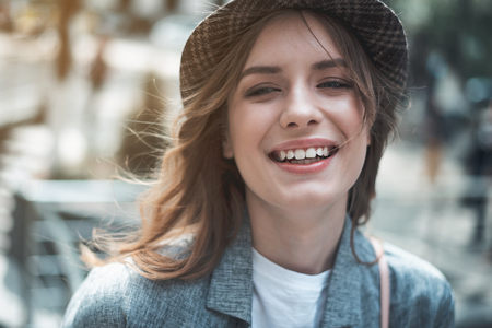 Portrait of beautiful girl laughing outside. She is looking somewhere with joy and wearing stylish hat. Happiness concept Stock Photo