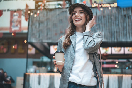 Smiling young lady is standing outside with cup of coffee. She is wearing trendy hat and looking up with pleasure
