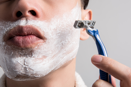 No beard. Close up half of face of pleasant cute guy is holding personal razor and shaving stubble from his chin. Male beauty and skincare concept Stock Photo
