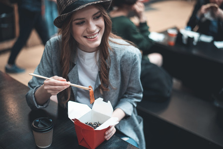 Smiling young lady is eating in Asian restaurant with chopsticks. She is sitting at the table looking away. Cup of coffee is near her meals