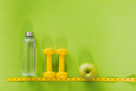 Top view of empty bottle, yellow dumbbell and apple put in row above tape measure. Close up