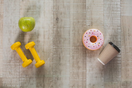 Sport and health versus harmful habits. Top view of green apple and yellow dumbbells lying opposite to coffee cup with donuts on wooden floor. Close up Stock Photo