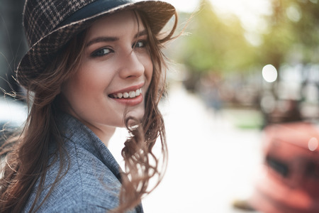 Grinning attractive lady in trendy hat is having wind in hair. She is looking at camera with joy. Copy space in right side Stock Photo