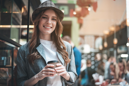 Waist up portrait of grinning lady holding hot drink. She is wearing trendy hat and looking at camera while standing in cafeteria