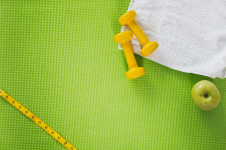 Top view of white towel, green apple and yellow dumbbells from lying on green carrymat. Tape measure is lying in left corner. Close up