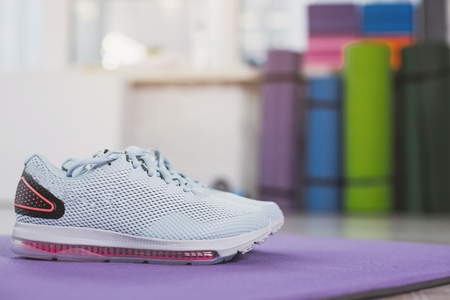 Sport is waiting. Focus close up of blue sneakers put on carrymat with exercising equipment in background. Copy space in right side