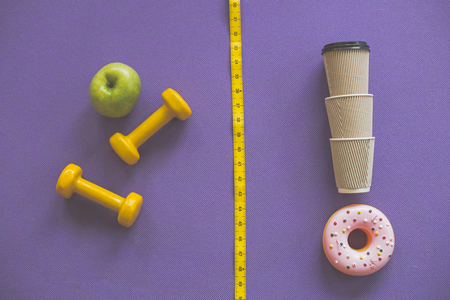 Top view of green apple with yellow dumbbells contrasted to coffee cups with donut on other side Stock Photo