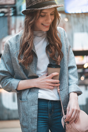 Cheerful young lady in trendy hat is standing outside. She is holding hot drink and looking down Stock Photo
