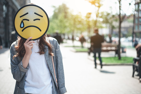 Lady is standing in the street and hiding face behind upset emoticon with falling tear. Sadness concert. Copy space in right side Stock Photo