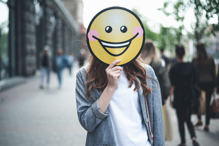 Cheer up. Waist up portrait of lady is standing in the street with yellow laughing emoticon. She is replacing her face with smiley Stock Photo