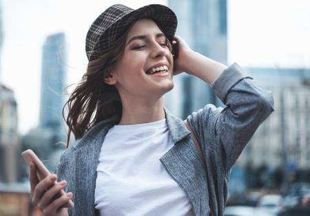 Cheerful young woman in trendy hat is having fun outdoors. She is holding smartphone in one hand and raising another to touch hair. She is closing eyes with enjoyment Stock Photo