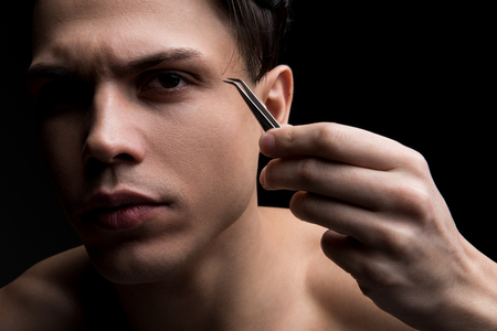 Close up portrait of young attractive guy is plucking eyebrows with concentration. He is standing and holding tweezers while looking at camera seriously.