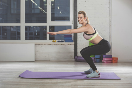 Full length of joyful pretty woman in good physical shape doing crouch exercises. She is smiling and content. Copy space in left side Stock Photo