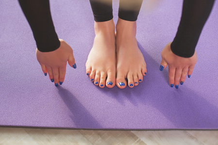 Close up of woman feet and hands on purple sport mat. Her blue-colored polished fingers are touching floor. Top view