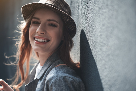 Portrait of laughing woman in stylish hat. She is looking at camera. Copy space in right side