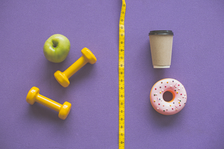 Two sides of lifestyle. Top view of apple and barbells compared to coffee and  donut on purple carrymat. They are divided by yellow tape measure 写真素材