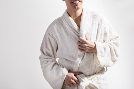 Good start of day. Close up of torso of optimistic young man in white terry cloth bathrobe is standing against light background. He is expressing gladness. Daily hygiene concept