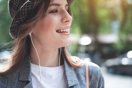 Profile portrait of joyful young woman listening to music with headphones. She is wearing stylish hat and looking side with joy