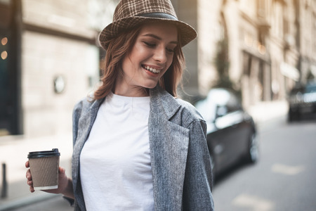 Smiling young woman in trendy hat is holding hot drink. She is walking n the street and looking down