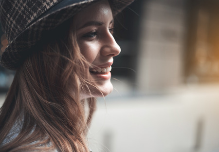 Close up profile of cheerful beautiful girl. She is wearing stylish hat outside and laughing. Happiness concept. Copy space in the right side