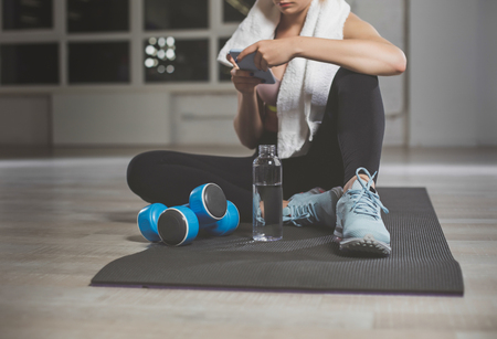 Close up of pretty female in fitness room. Woman looking on mobile in comfortable position on floor. Dumbbells and bottle of water are nearby