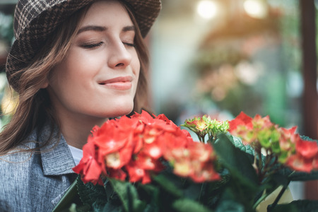 Focus on smiling lady in trendy hat with red bouquet. She is smelling blossom and happily closing eyes Stock Photo