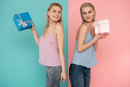 Waist up portrait of two attractive cheerful ladies posing with beautiful boxes. blue and pink background Stock Photo