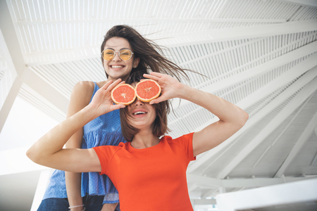 Low angle of joyful young women are fooling around at summer house. Girl is closing her eyes by citrus fruit and smiling