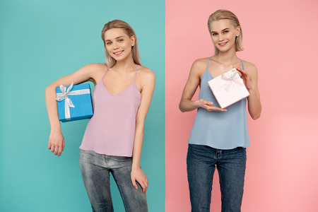 Portrait of two smiling girls holding gift boxes and looking at camera with joy. blue and pink background Stock Photo