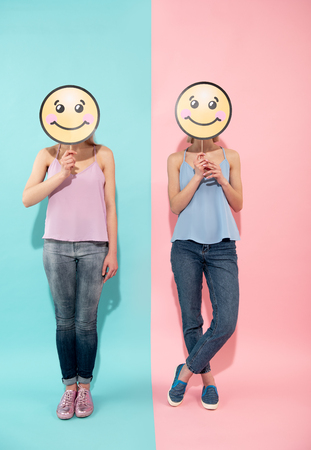 Full length of two happy young women posing on blue and pink background. They are in t shirts and jeans