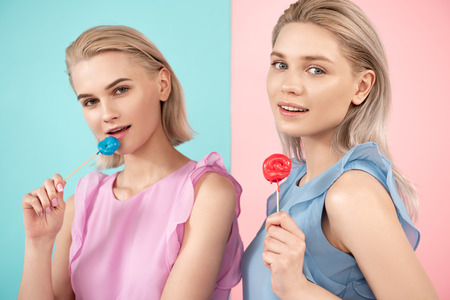 Portrait of young ladies taking pleasure in eating candies. Isolated on blue and pink background