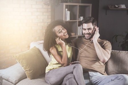 Portrait of cheerful young couple in love is listening to music while resting at home. They are wearing earphones and using player on phone. Girl is looking at camera with joy