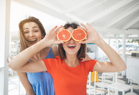 Waist up portrait of excited two girls are having fun on summer vacation. One lady is covering her eyes by orange. Her friend is standing and laughing