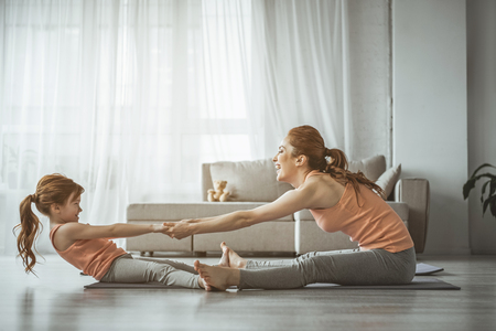Full length portrait of little girl trying to outweigh her mom during sport exercise on the floor. Both looking very happy and smile Standard-Bild