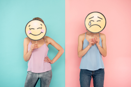 Waist up of smiling girl and her crying female friend posing on blue and pink background