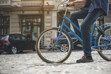 Male feet pedaling bike on stony street. Copy space in left side