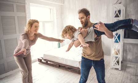 Doting father is holding son while little boy is showing arms like flying. Joyful mom is replicating kid behavior acting like plane. Loving parents and child are having fun in bright bedroom