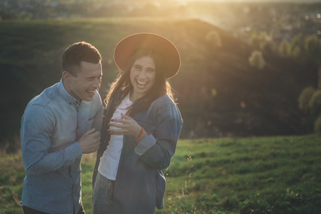 Happy together. Waist up portrait of young female and male standing close to each other on green hill during sunset with sincere vivid smiles on faces. They are having fun together. Copy space in right side Imagens