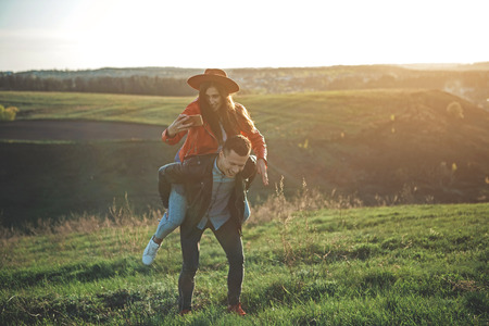 Happy in love. Full length of full of happiness and joy couple in summer evening nature. Boy is carrying girl with cellphone in hand. They are smiling and having fun together