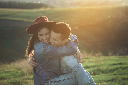Cuddles of happiness. Waist up of joyful young couple standing on meadow in summer evening. They are holding each other tightly with wide sincere smiles and youth energy