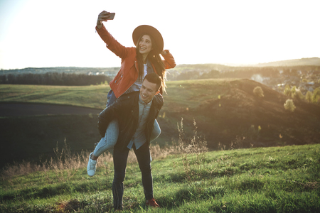 Forever young. Full length of laughing female and male surrounded by wonderful green hills. Woman is making selfie on back of boyfriend. Copy space in right side