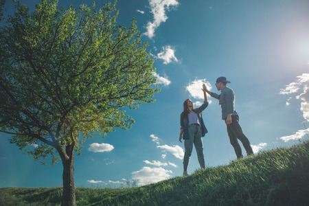 Love me like you do. Low angle full length of girl and boy standing on green hill among beautiful summer nature and touching hands. They are calm and happy with amazing blue sky on background