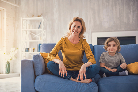 Smiling parent is sitting with her delighted kid on sofa. They are happily spending time together in cozy apartment and looking at camera. Mom and son together concept 写真素材
