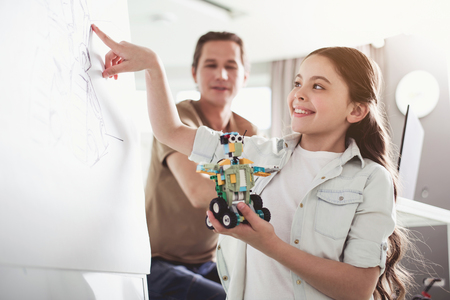 Positive girl pointing at board with image while keeping robot in hands. Modern education concept