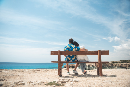 Wonderful day. Full length back view of romantic couple is enjoying seascape while sitting on the bench. Guy is hugging girl tenderly while resting with colorful blue sky in background. Copy space Stock Photo